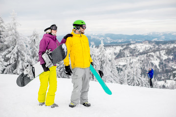 Young couple walking with snowboards during the winter vacation on the snowy mountains