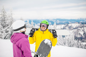 Young couple in winter sports clothes talking together with snowboards during the winter vacation on the snowy mountains