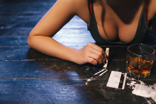 Woman getting ready to sniff cocaine. Drug addiction. In need of one more dose. Detrimental lifestyle