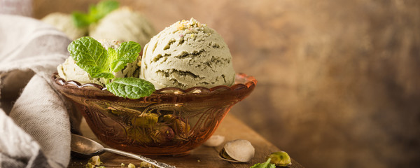 Scoop of homemade pistachio ice cream with chopped pistachios in red glass bowl on old wooden table background. summer food concept with copy space. Banner.