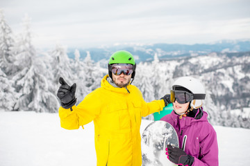 Young couple in winter sports clothes talking together standing with snowboards during the winter vacation on the snowy mountains