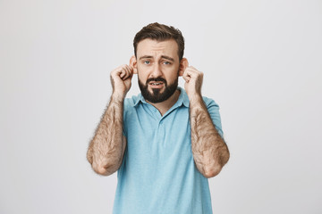 Adult bearded man with gloomy smile stretching ears, imitating sad monkey, over gray background. Guy is tired of hearing lies from his close friends. Fed up of listening demands