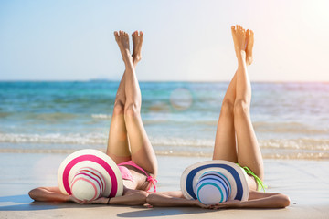 two woman in bikini lie on the sand on the sea beach for sunbath, enjoy and happy relax on the beach