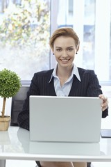 Portrait of happy businesswoman with laptop