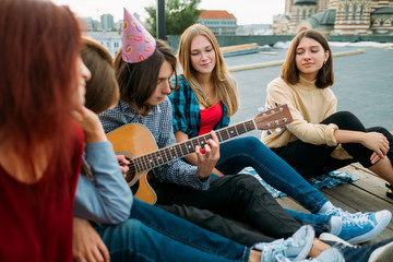 Group of friends listen to busker playing guitar at a roof top party. Musician artistic lifestyle. Teenagers leisure