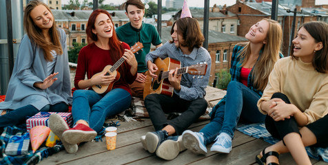 Group of friends hangout. Singing to a guitar. Free spirits lifestyle. Urban hipster teenagers leisure