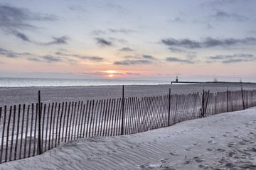 Sunrise over beach with wooden fence