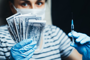 Money and syringe in the hands of the girl on a black background