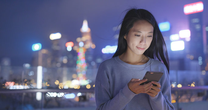 Asian Woman look at smart phone in city at night