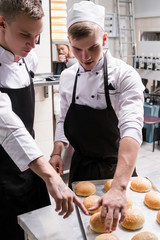 Freshly baked hamburger rolls. Young cooks checking the quality of the buns looking for flaws and seeking perfection. Communication and teamwork concept