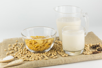 Soy milk in glass and sereal ,garnish in wooden spoon.