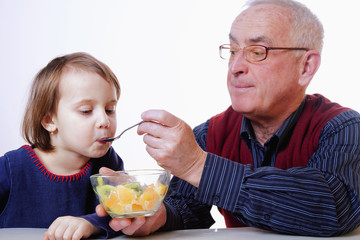 Grandpa feeding his grandchild with fruits salad. (Healthy foods, vitamins, love, generation, relationship concept)