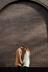 Love and dating. Young couple hold hands. Romantic relationship and happiness. Brick wall copy space background