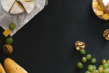 Tasting cheese dish with nuts and fruits on black table. Menu design horizontal