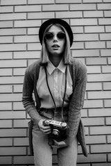 Fashion girl posing on brick wall background. Retro