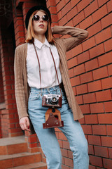 Young woman in sunglasses with a camera walking in the city. Journalist