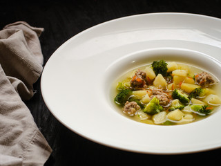 vegetable soup with meatballs and broccoli in a white plate