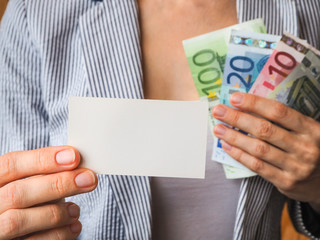 Business card on the background of Euro banknotes in the hands of a business woman
