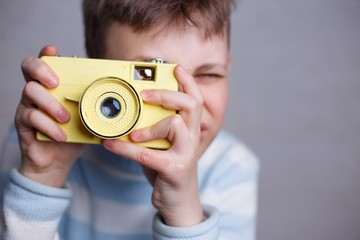 Boy taking a picture with vintage camera. Photography, hobby and leisure concept