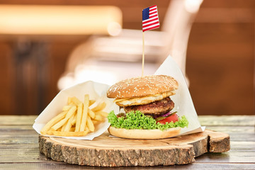 Set of unhealthy food. American burger and French fries on wooden board.