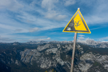 Warning sign for falling off a cliff or mountain. There are mountains in the background indicating the danger.