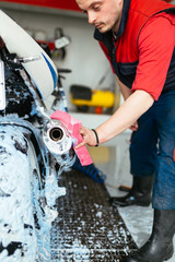 A man cleaning motorcycle with sponge using blue foam, car detailing (or valeting) concept. Selective focus.