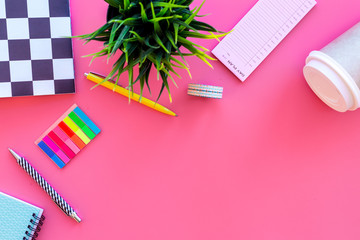 Student's desk. Notebook, stationery, coffee cup on pink background top view copy space