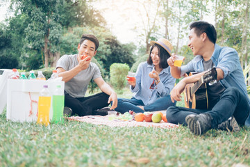 Young teen groups having fun picnic in park together.