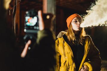 Photographer shooting model at night