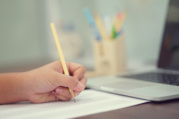 close up student woman hand (left) using pencil for doing text exam after finish course online learning , self study education concept