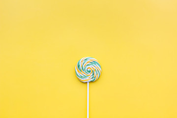 Colorful lollipop swirl on yellow pastel background top view copy space