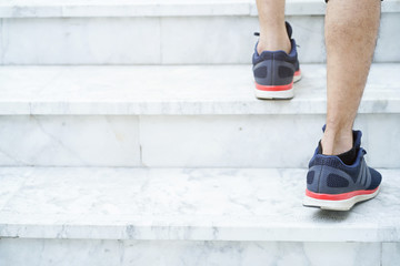 close up runner man wearing sport shoes and step up on stair for prepare to playing , workout cardio concept