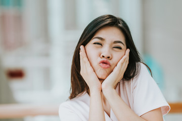Asian woman making funny face expression with hands cover her cheek indoor