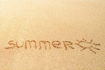 Word SUMMER written in the sand on a beach with drawing of the sun