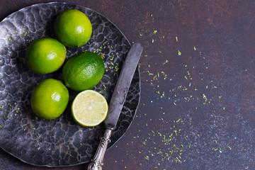 fresh green limes in black bowl, dark background