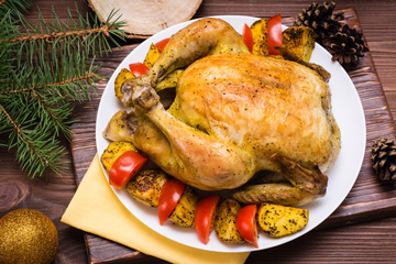 Baked whole chicken with a garnish of potatoes and tomatoes on a plate. Christmas decoration