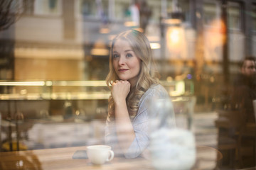 Charming blonde woman sitting at the cafe