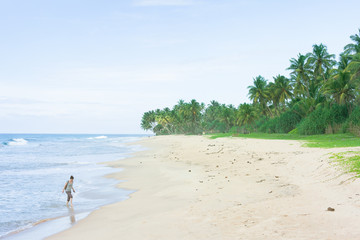 Balapitiya Beach, Sri Lanka - A woman walking in the surge at the beacof Balapitiya