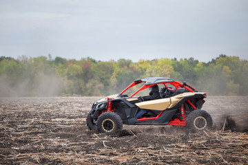 Red quad bike with a driver in plowed field