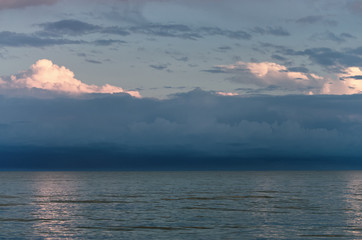 Fotomurais - Large storm clouds on the Azov Sea, illuminated by the setting sun, the sea horizon. Reflection on the water surface.