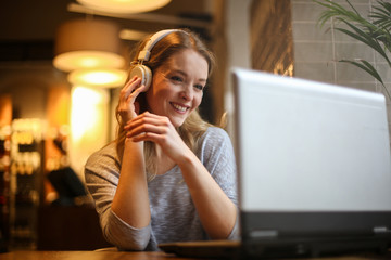 Smiling woman using laptop and headphones