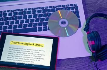 Laptop und Tablett auf dem der Text einer Unterlassungserklärung angezeigt wird in englisch Unterlassungserklärung mit einer DVD und einem Kopfhörer