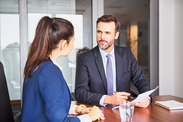 Recruiter during business job interview in office with female candidate