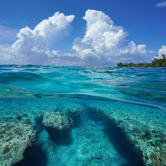 Seascape over and under sea surface, cloudy blue sky with a rocky seabed underwater split by waterline, outer reef of Huahine island, Pacific ocean, French Polynesia