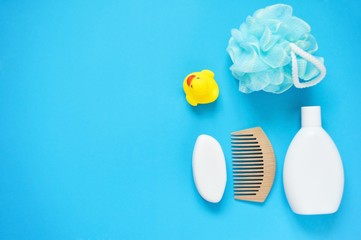 Baby bath products/ Yellow rubber duck, soap, shampoo, wooden hair brush and sponge on a blue background