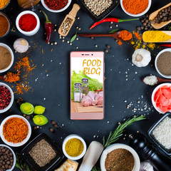 Food blog concept. Indian spices, herbs and smartphone on black background