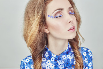 Woman with pigtails and blue flowers on the eyelashes, skin care, facial care and eyelashes. Fashion art girl makeup, natural cosmetics, anti-wrinkle treatment. Portrait of a woman large