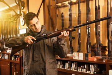 Portrait of young confident man showing rifle