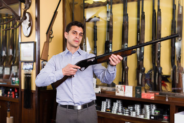 Cheerful male hunter choosing shotgun in store