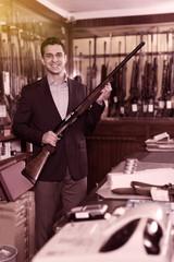 Positive male seller in hunting shop demonstrating shotgun